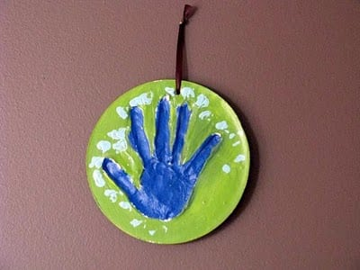 child plaster hand print hung on wall