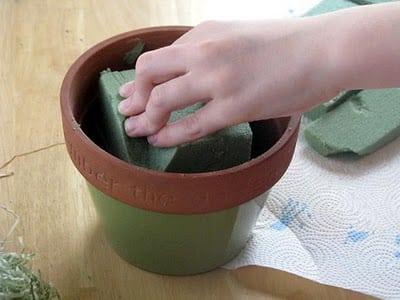 hand placing floral foam into flower pot