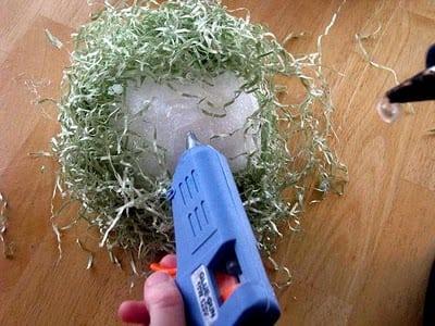 hand hot gluing craft grass onto styrofoam ball