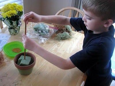 child placing dowel into floral foam