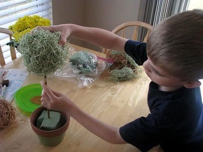child placing styrofoam ball on top of wooden dowel