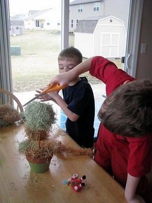 child trimming craft grass on styrofoam ball
