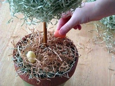 child adding small plastic eggs inside pot