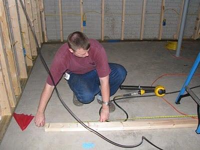 man framing basement wall