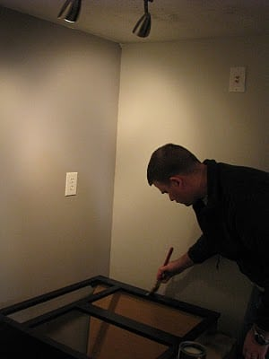 man painting cabinet with black paint