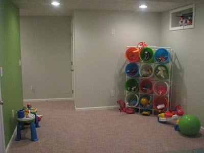 carpeted room with toy buckets