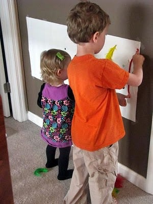 two children decorating sticky poster on wall