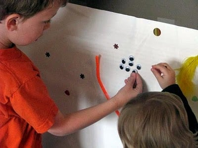 child adding craft eyes to sticky poster
