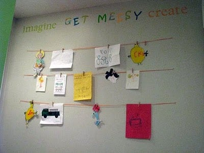 children's artwork displayed on wall hanging on string