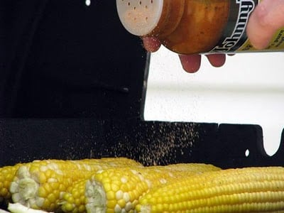 hand sprinkling salt on corn