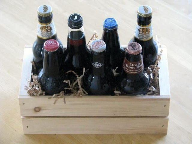 wooden crate with variety of roobeer bottles and shredded paper