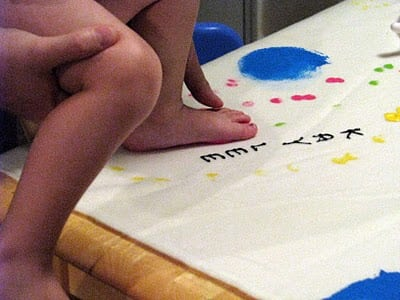 child printing footprint with paint on blanket