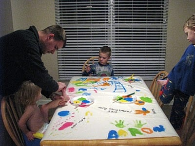 dad helping kids paint on fleece
