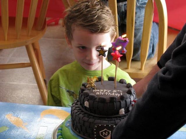 child blowing out candles on castle cake