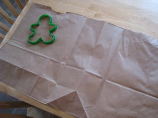 brown bag laid flat with gingerbread cookie cutter