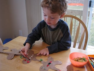 toddler decorating brown bag gingerbread man