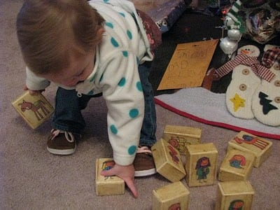 toddler playing with nativity blocks