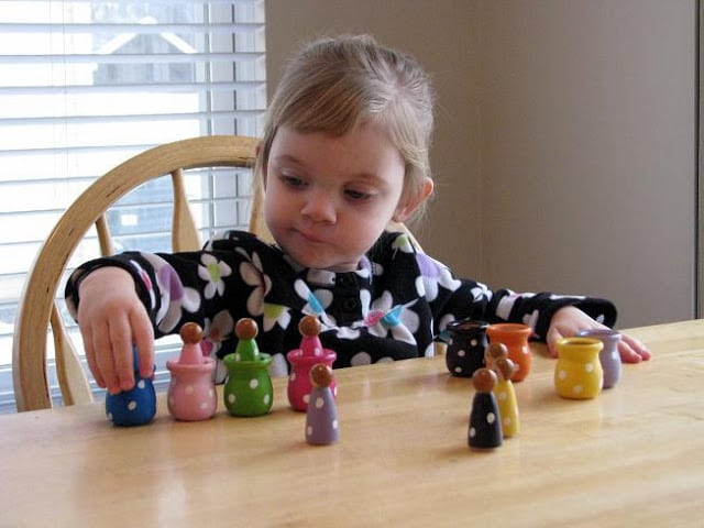 little girl playing with matching and sorting dolls on table