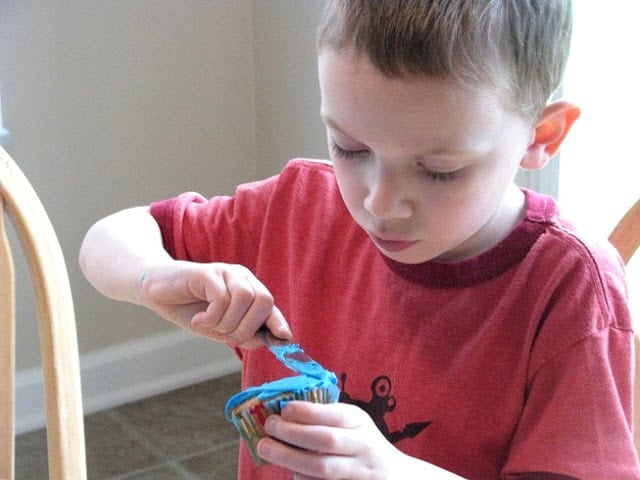 child frosting cupcake with blue frosting