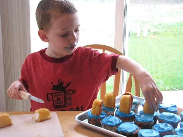 child putting half of a Twinkie onto cupcake