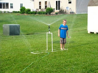 child playing with homemade pvc pipe sprinkler