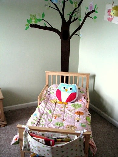 wooden toddler bed with pink comforter