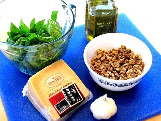 cheese basil garlic nuts and oil on a cutting board