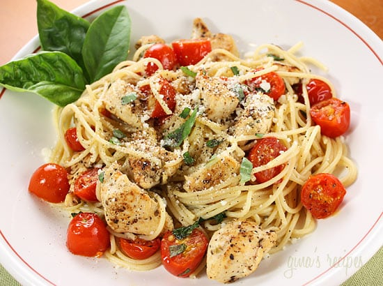 white plate with spaghetti chicken tomatoes and basil