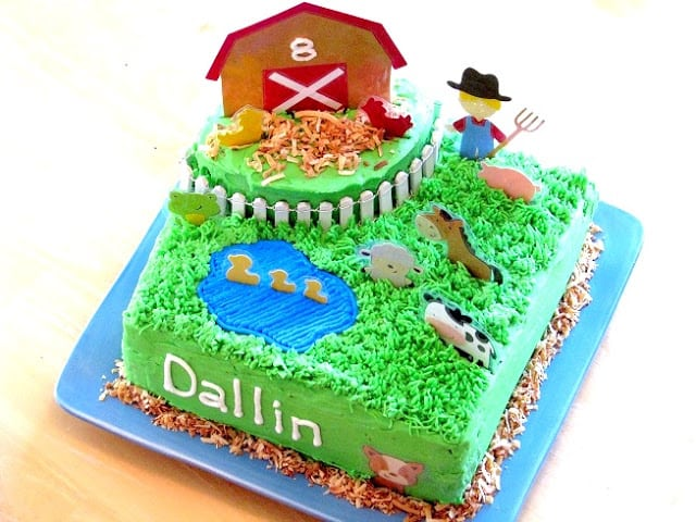 square barnyard themed cake on blue plate
