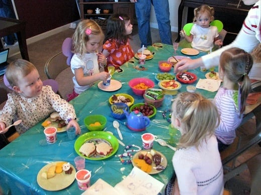 little girls sitting around table for birthday party