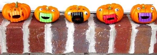 mini vampire pumpkins lined up on on brick ledge