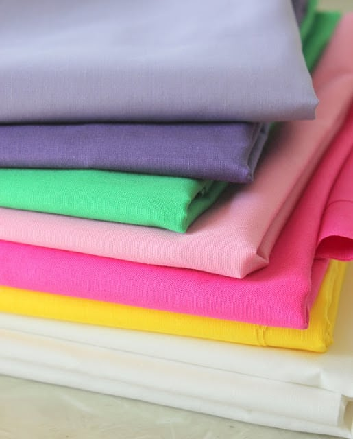 stack of suggested broadcloth fabrics for princess apron pattern