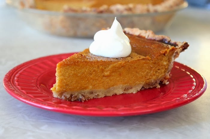 slice of pumpkin pie with whipped cream on plate