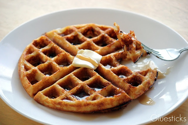 waffle on plate with fork cutting out a piece