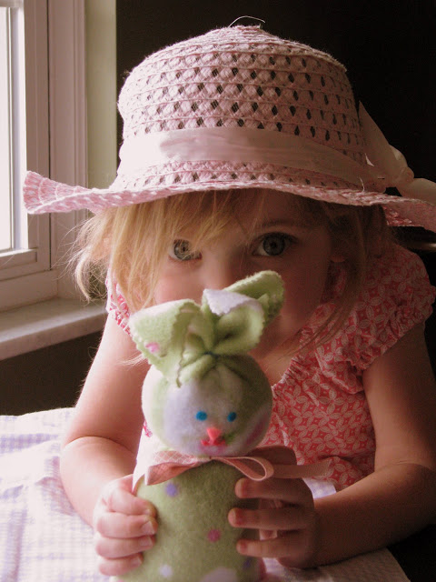 little girl peeking out from behind bunny