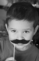 child holding up pretend mustache photo prop
