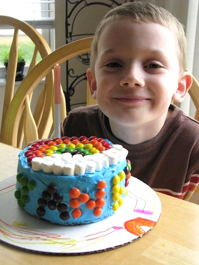 child with finished rainbow skittle cake