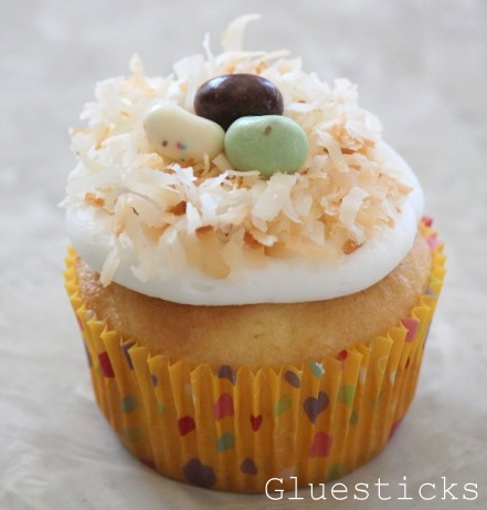vanilla cupcake with frosting toasted coconut and jelly beans on top