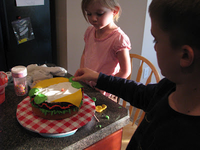 child adding fondant pickles to cake