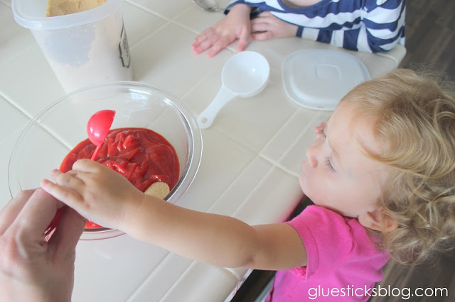 toddler hand pouring in a teaspoon of garlic powder
