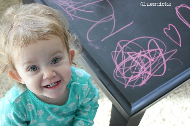 little girl next to chalkboard table