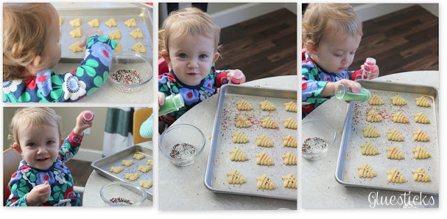 toddler adding sprinkles to cookies