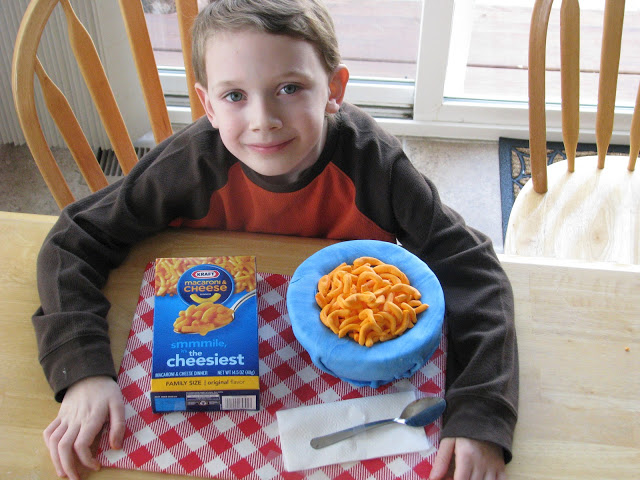child with finished macaroni and cheese cake