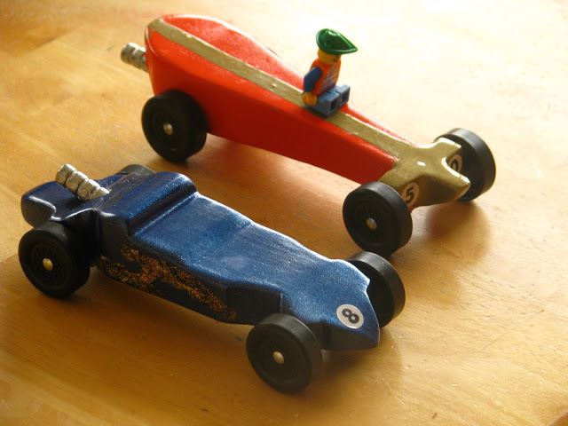 two wooden pinewood derby cars