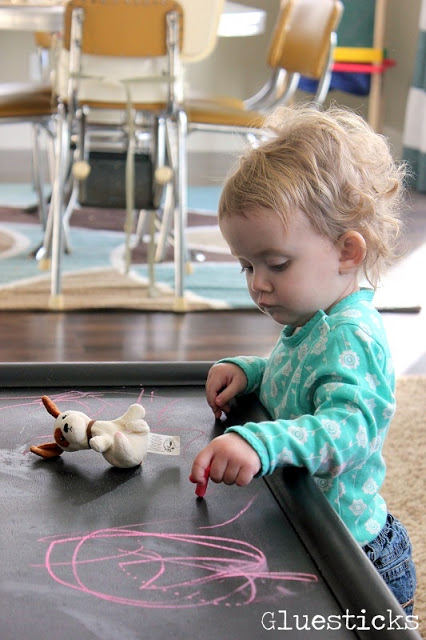 toddler drawing on chalkboard table