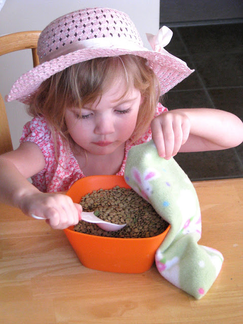 toddler filling bunny with lentils