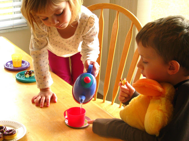 child pouring water from toy tea pot