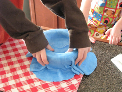 child covering round cake with blue fondant