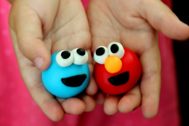 hands holding Cookie Monster and Elmo character