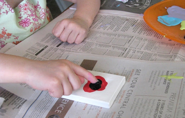 child painting flower on canvas with finger